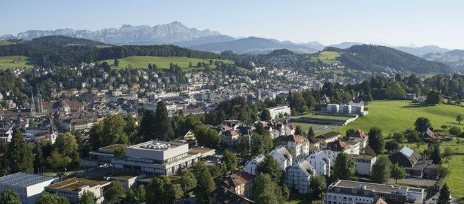 Luftaufnahme über St.Gallen mit dem Alpenstein im Hintergrund und der Unviersität St.Gallen im Vordergrund